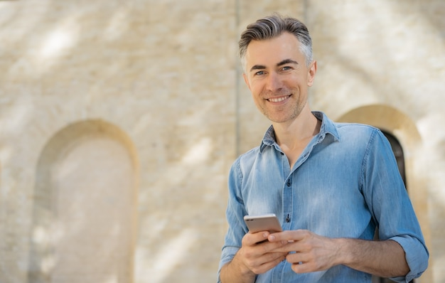 Handsome mature man using mobile phone