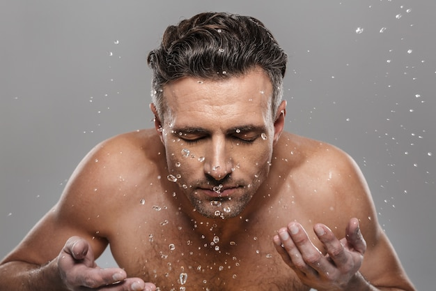 Handsome mature man washing his face.