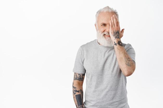 문신을 한 잘생긴 성숙한 남자, 얼굴의 절반을 숨기고, 손으로 눈을 가리고 앞에서 행복하게 웃고, 흰 벽에 회색 티셔츠를 입고 서 있습니다.