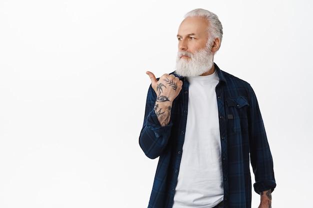 入れ墨を指しているハンサムな成熟した男、自信を持って決心した顔で左を見て、広告のロゴを表示し、白い壁に立っている