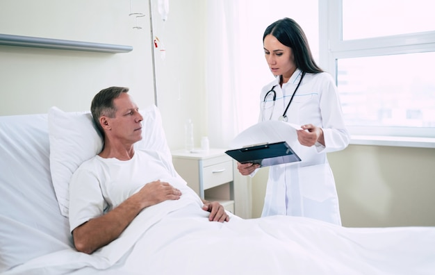 Handsome mature patient man is lying on the clinic bed and has a conversation with a confident young woman doctor in a white coat