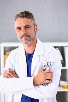 Handsome mature smiling male doctor with arms crossed on chest
