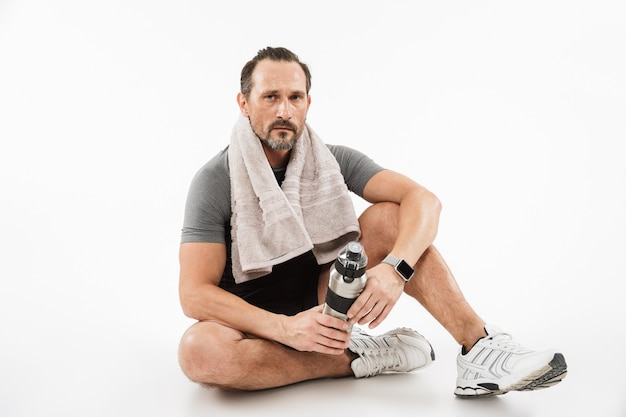 Handsome mature sportsman sitting with towel and water