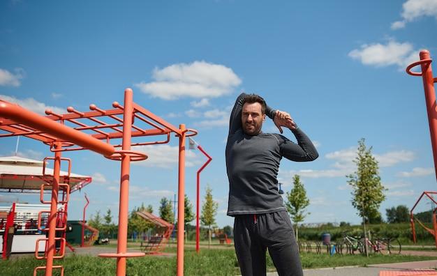 野外でスポーツグラウンドでトレーニングする前に、背中の後ろで腕を伸ばしているハンサムな成熟したスポーツマン。若い大人の40歳のヨーロッパのスポーティな男が美しい晴れた日に屋外でトレーニングを楽しんでいます