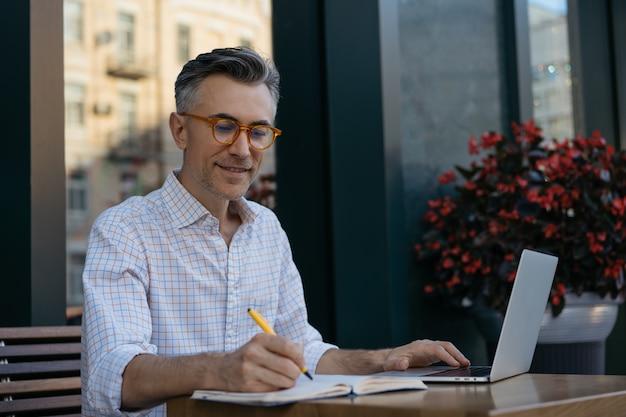 Красивый зрелый писатель делает заметки в записной книжке. бизнесмен, работающий, планирование запуска