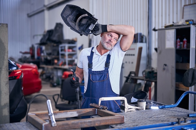 Handsome mechanic holding welding torch and protective helmet