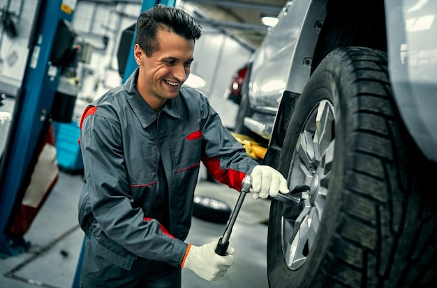 Handsome mechanic in uniform is working in auto service. car repair and maintenance. holding car wheel.