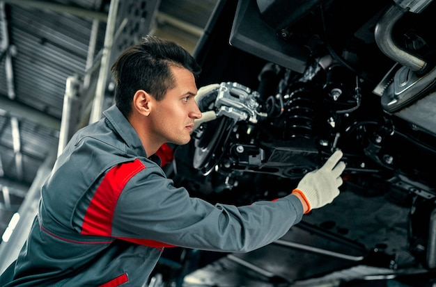 Handsome mechanic in uniform is working in auto service. car repair and maintenance.