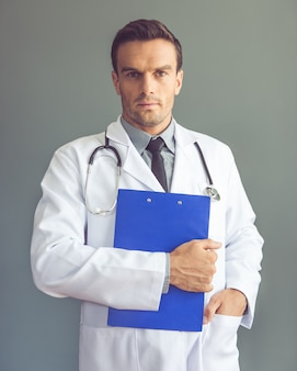 白いコートでハンサムな医師がフォルダーを保持しています