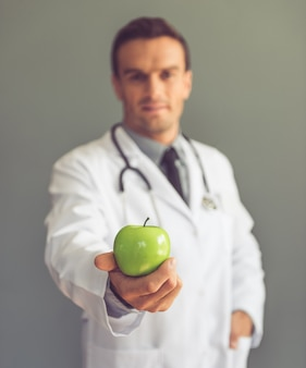 Handsome medical doctor in white coat is holding an apple. diet concept