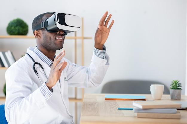 Красивый медицинский работник сидит в полу-положении, держа руки в воздухе