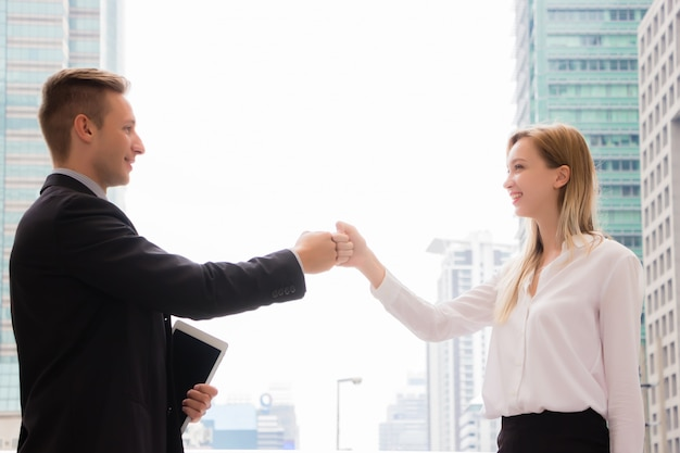 Handsome men and beautiful women, they dress in formal attire and are greeted by fist bump or knuckle bump, having a high-rise building background in the morning in the concept of meeting for business