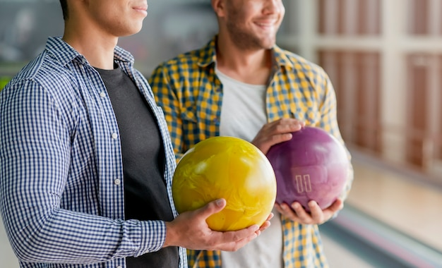 Handsome men holding colorful bowling balls