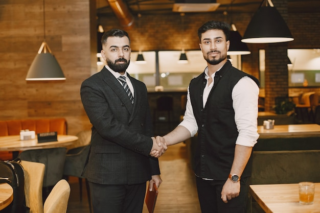 Handsome men in a restaurant, shaking hands