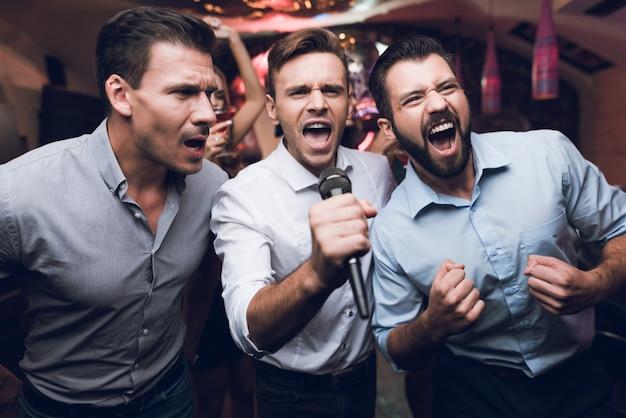 Handsome men singing karaoke in club