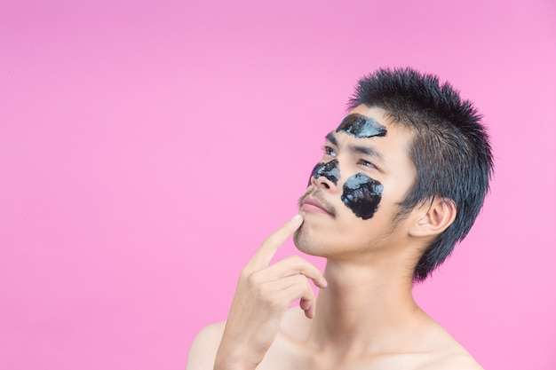 Handsome men who apply black cosmetics on their faces, showing various postures with a pink .