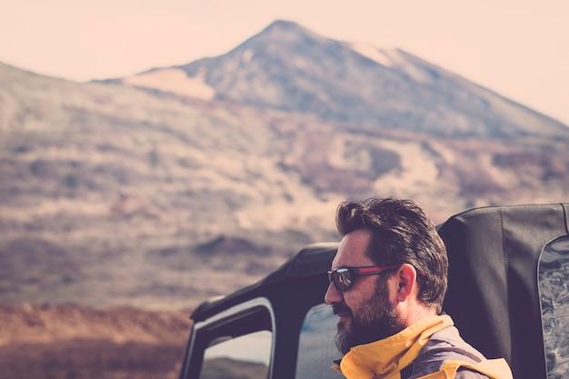 あごひげとサングラスの肖像画を持つハンサムな中年男性。オフロード車とテイデバルカン山脈