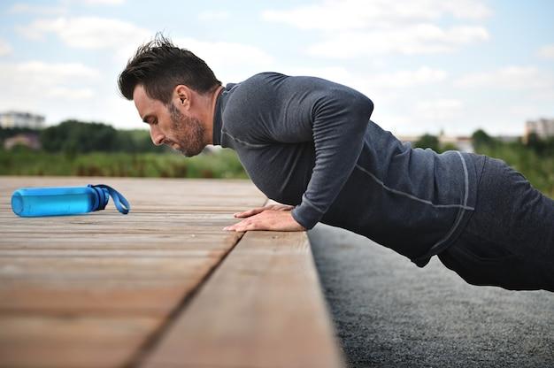 잘생긴 중년 운동선수는 야외 스포츠를 하고 운동장에서 팔굽혀펴기를 합니다. 활동적이고 건강한 생활 방식, 야외 운동의 개념