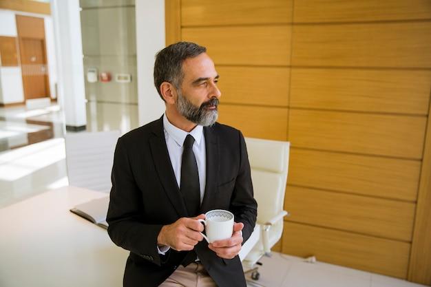 一杯のコーヒーまたはオフィスを保持しているハンサムな中年のビジネスマン