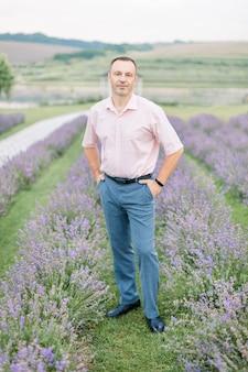 ラベンダー畑でカメラにポーズをとって、明るいシャツと青いズボンのハンサムな中年白人男性