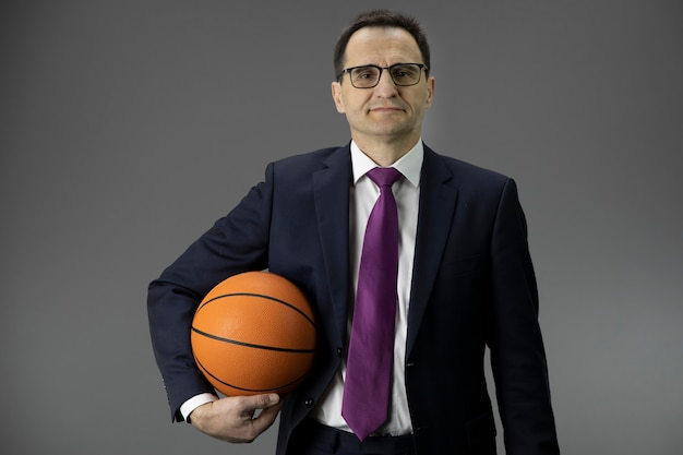 Handsome middle aged man in formal clothes holds basketball in hand. copy space