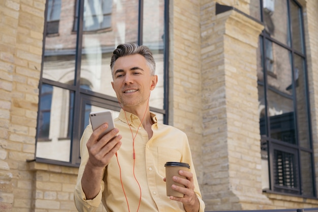 Handsome middle aged man holding mobile phone, drinking coffee, reading news