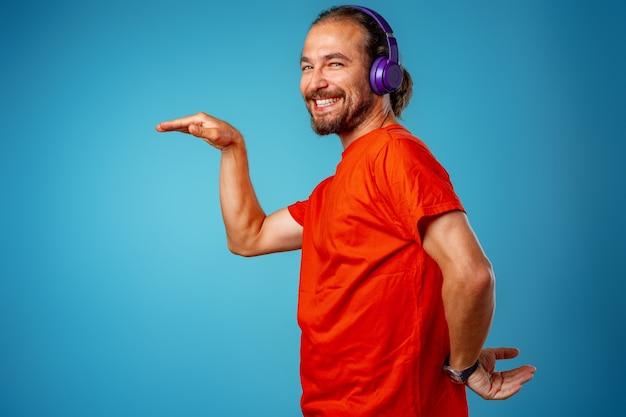 青いヘッドフォンで音楽を聴いているハンサムな中年男性