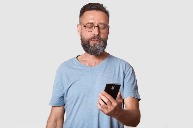 Handsome middle aged man using his phone with serious faxcial expression while standing against gray wall attractive male reading important message from wife. people and technology concept.