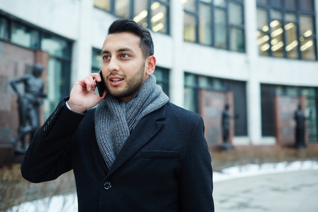 Handsome middle-eastern man speaking by phone in city