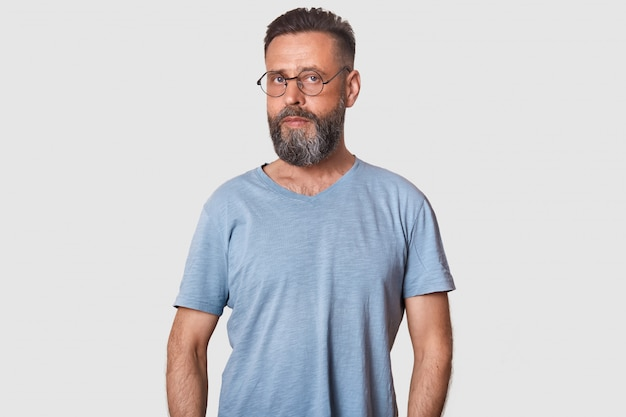 Handsome middleaged man, having serious facial expression, malewearing casual clothing and rounded optical glasses, posing isolated on white.