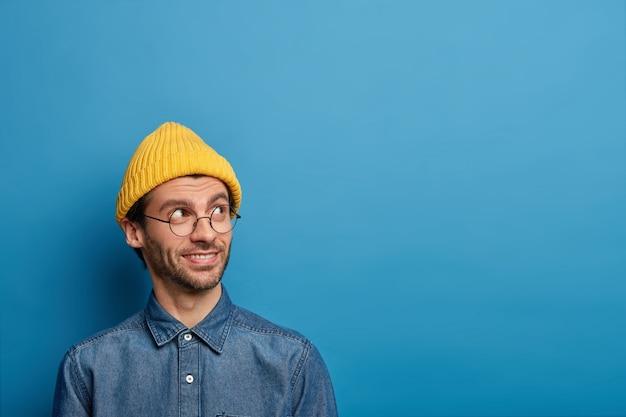 잘 생긴 밀레 니얼 소년은 기쁜 표정으로 옆으로 보이고, 노란 모자와 데님 셔츠를 입고, 흥미로운 생각이나 욕망을 가지고 있습니다.