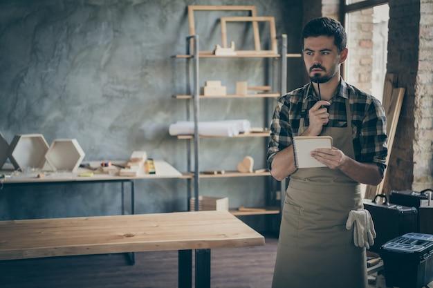 Красивый мыслящий парень продавец администратор замечает заказ клиента подробности пожелания бумажный дневник ручка деревянный бизнес деревообработка магазин гараж в помещении