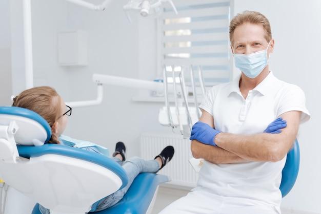 치료가 필요한 작은 환자의 방문을 받고 의사의 의자에 앉아 잘 생긴 신중한 저명한 의사