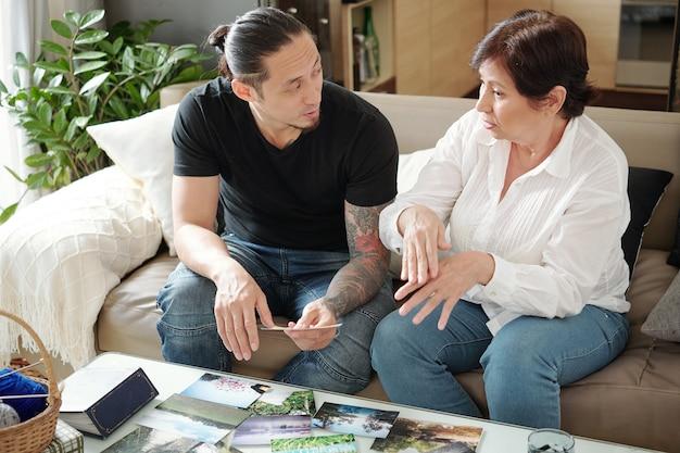 Красивый смешанный мужчина показывает фотографии из поездки к зрелой маме и рассказывает о своих приключениях.