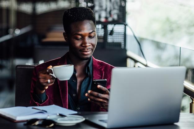 Красивая модель, африканский молодой человек на летней террасе, читая новости по телефону.