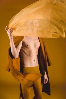 透明な布を保持しているハンサムなモデル