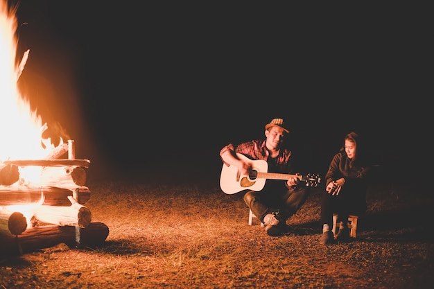 Handsome model man playing guitar with friends in forest with bonfire