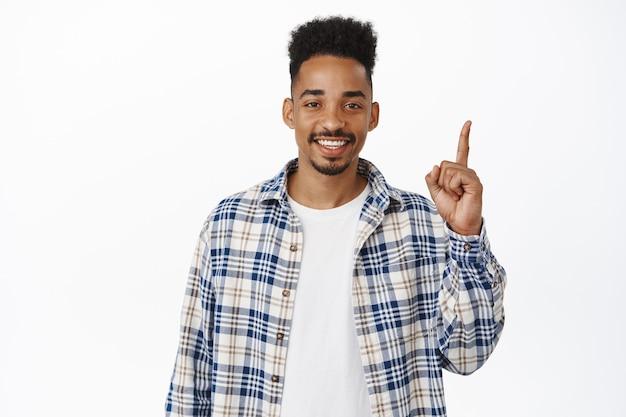 Bel ragazzo afroamericano moderno di 20 anni, puntando il dito verso l'alto e sorridendo felice con i denti bianchi, mostrando pubblicità, studio