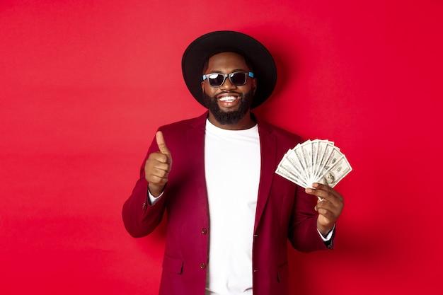 Bell'uomo afroamericano moderno in occhiali da sole e abiti da festa, mostrando pollice in su con dollari, guadagna soldi e sembra soddisfatto, sfondo rosso.