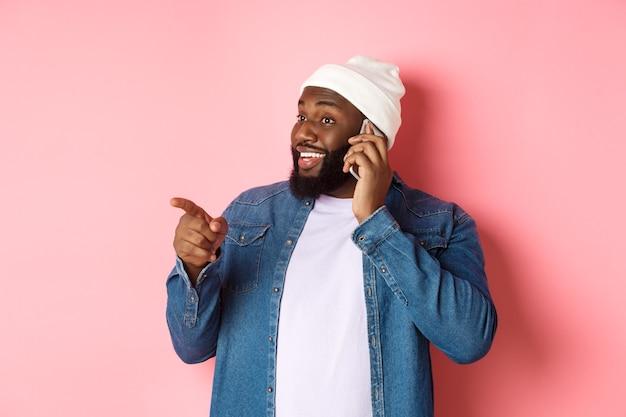 Красивый современный темнокожий мужчина разговаривает по мобильному телефону, указывая влево на человека и улыбается, стоя на розовом фоне