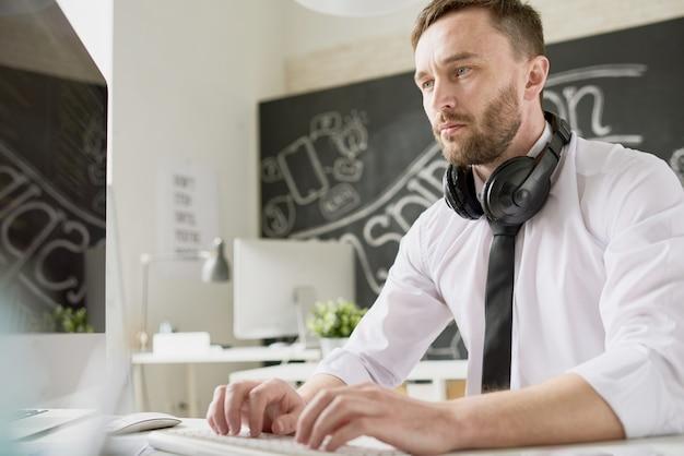 Handsome modern businessman typing