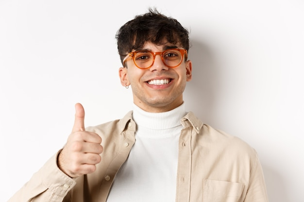Handsome modern guy in glasses and earring, smiling satisfied and show thumb up, recommend company, standing on white wall.