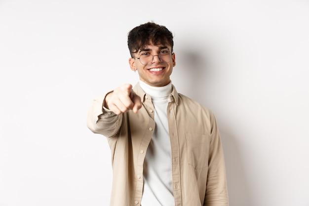 カメラを指して、笑顔であなたを選んで、白い背景の上に立って、イベントに募集または招待する、眼鏡をかけたハンサムな現代人。