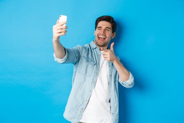スマートフォンで自分撮りを取り、モバイルカメラで人差し指を指して、生意気なウインク、青い背景に立っているハンサムな現代人