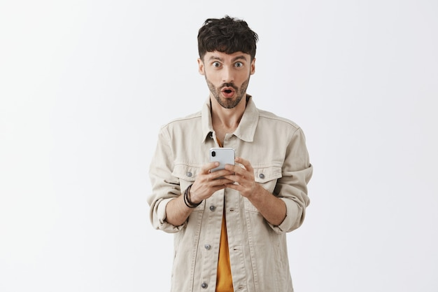 Handsome modern guy using mobile phone and looking surprised