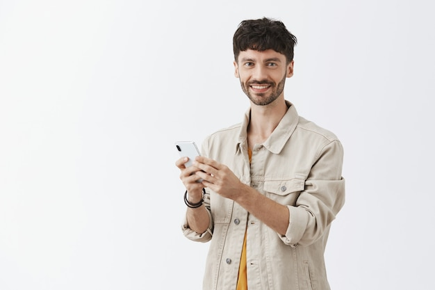 Handsome modern guy using mobile phone and smiling