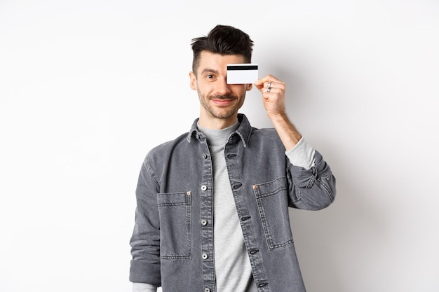 Handsome modern guy with moustache, standing in casual clothes and holding plastic credit card on eye, smiling pleased at camera, white background.