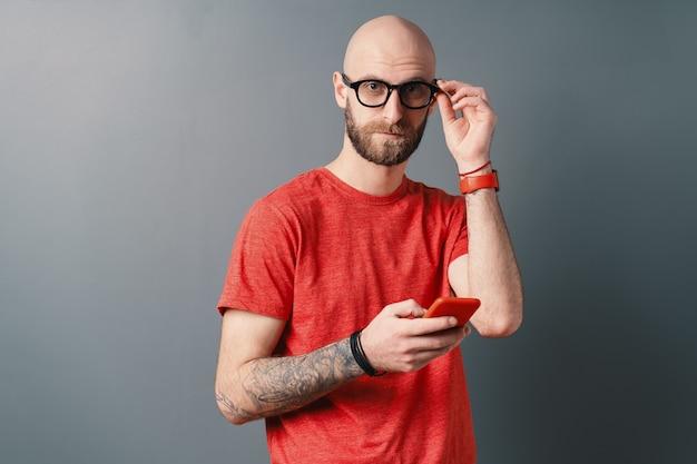Красивый современный лысый мужчина с бородой, красной футболкой, поправляет очки, пишет текстовые сообщения, держа смартфон
