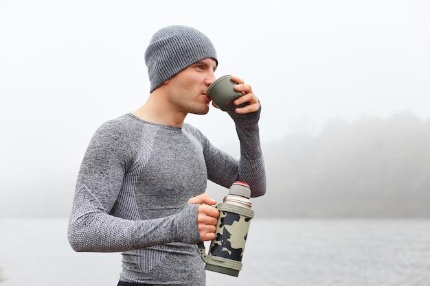 Красивый современный мужчина любит пить кофе и отдыхать у реки, мечтательно глядя вдаль и наслаждаясь горячим напитком.