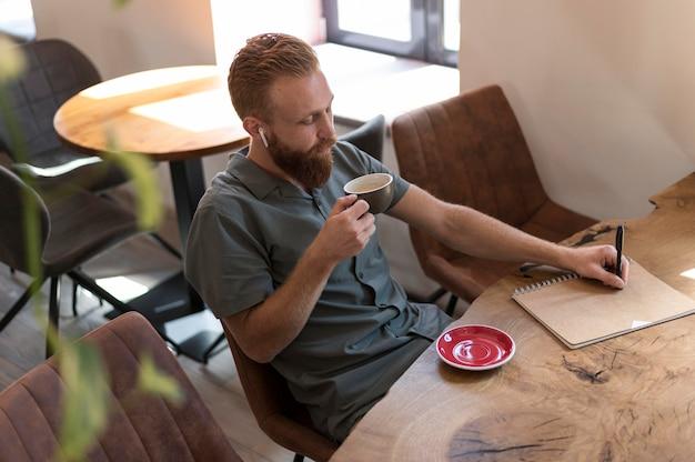 一杯のコーヒーを保持しているハンサムな現代人